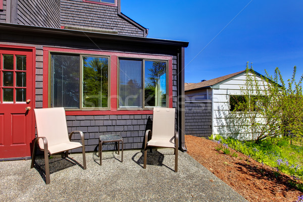 Two chairs next to red door and small black house. Stock photo © iriana88w