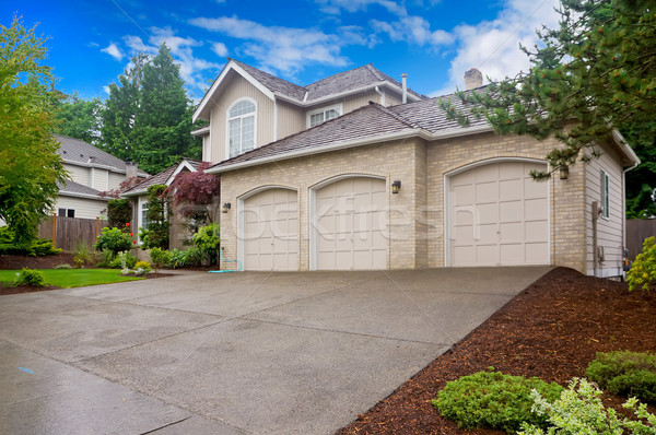 Stock photo: Large beige house with three car garage and large driveway.