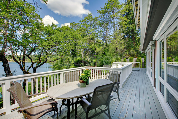 Large long balcony home exterior with table and chairs, lake view. Stock photo © iriana88w