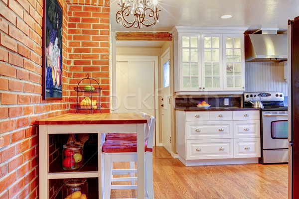 White kitchen with brick wall, hardwood and stainless steal stove. Stock photo © iriana88w