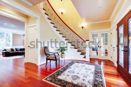Entrance with curved staircase and luxury rug with chair. Stock photo © iriana88w