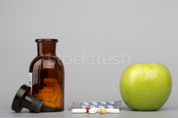 Stock photo: Green apple and colored pills with brown bottle