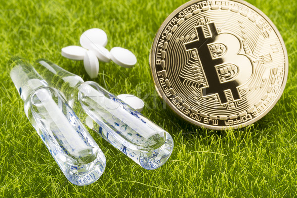 White pills and ampules with bitcoin coins on the grass background - healthcare cost concept Stock photo © ironstealth