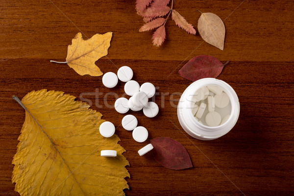 Heap of round white pills and pill bottle Stock photo © ironstealth