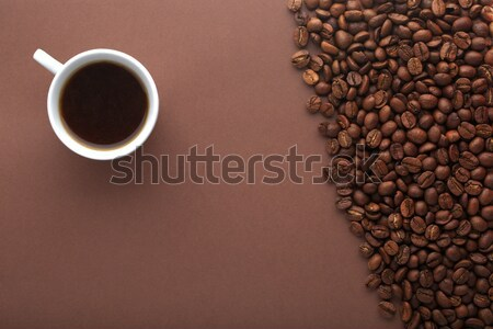 Hot coffee cup and beans on a brown background. Stock photo © ironstealth