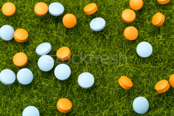 Orange and blue pills spilling on the green grass Stock photo © ironstealth