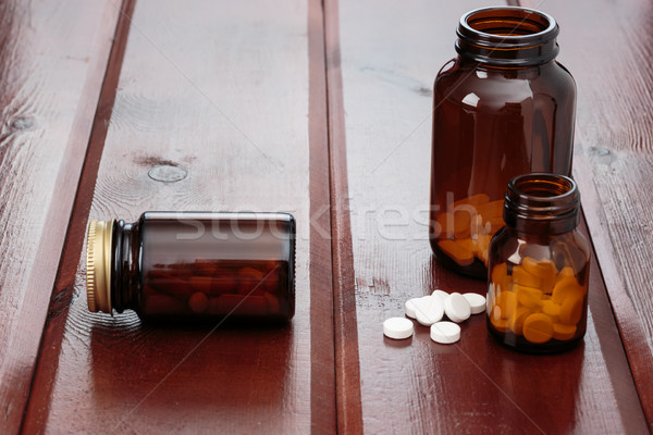 Pile of white pills and glass bottles for medicines on a wooden background Stock photo © ironstealth