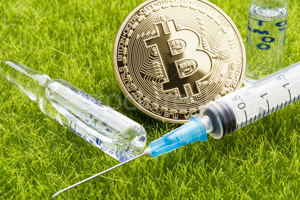 Ampoule and syringe with bitcoin coin - healthcare cost concept Stock photo © ironstealth