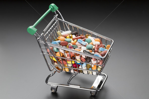 Shop cart with different colorful pills on black Stock photo © ironstealth