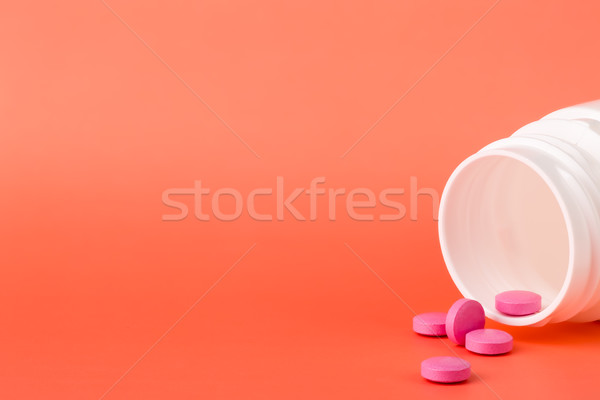 Stock photo: Pink pills and open medicine bottle