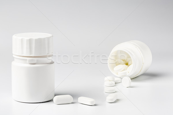 White plastic pill bottles and heap of various pills Stock photo © ironstealth