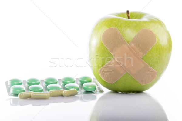 Green apple with a band-aid and varios pills Stock photo © ironstealth