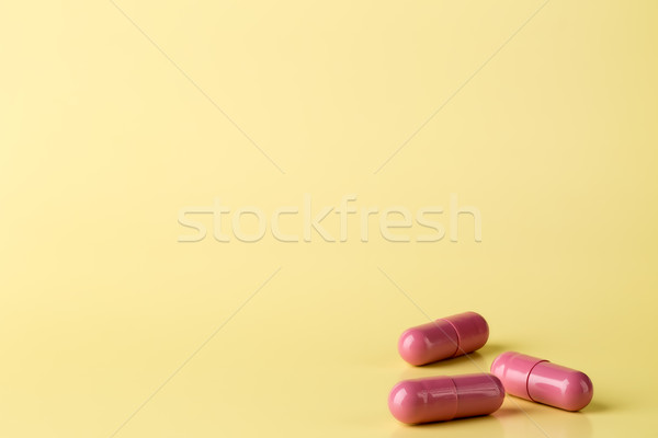 Stock photo: Red medicine pills on bright background