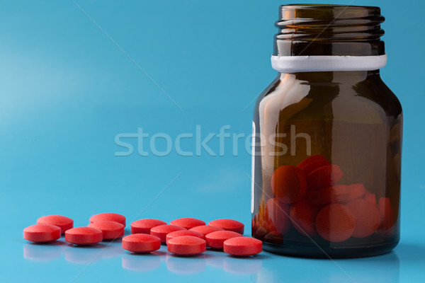 Round red pills and glass pill bottle Stock photo © ironstealth