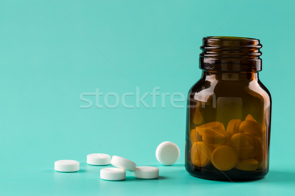 Brown glass pills bottle and white round pills Stock photo © ironstealth