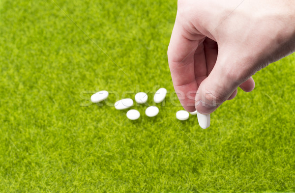 Male hand holding pill on background of tablets spilling on the grass Stock photo © ironstealth
