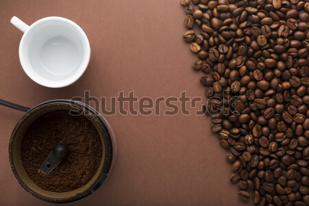 Cup of coffee, coffee grinder and beans on brown background. Top view. Focus on grinder Stock photo © ironstealth