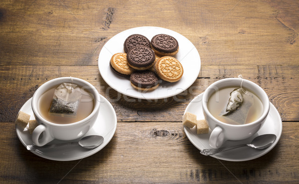 Set of two ceramic tea mugs with sachet and plates cookies. Stock photo © ironstealth