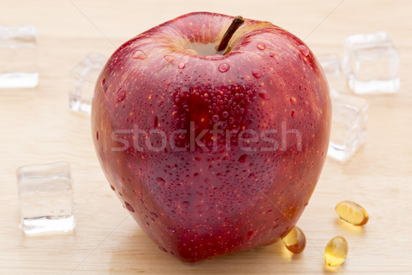 Fish oil pills and red apple on wooden background Stock photo © ironstealth