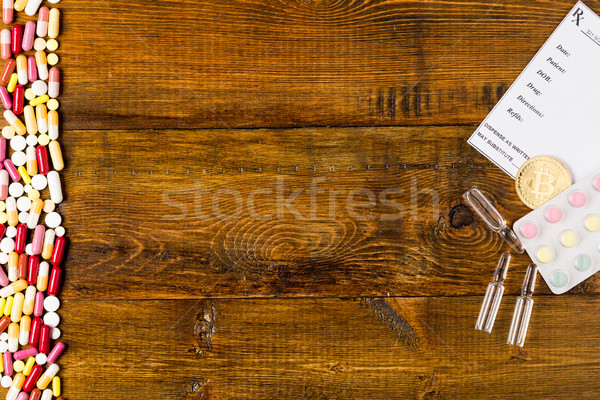 Border from various colorful capsules and pills on wooden background Stock photo © ironstealth