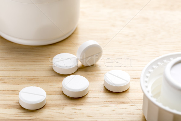 Pills and pill bottle on wooden background Stock photo © ironstealth