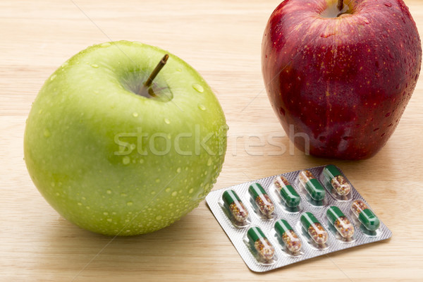Stock photo: Green transparent capsules blister pack and fresh apples