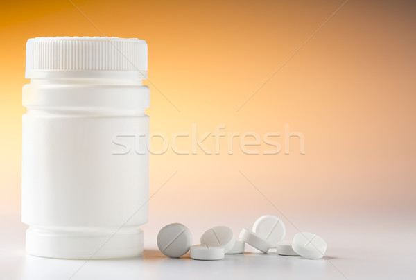 Plastic pill bottle and heap of round white pills Stock photo © ironstealth