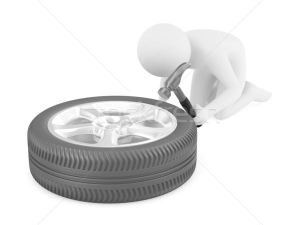 man repairs wheel. Isolated 3D image Stock photo © ISerg