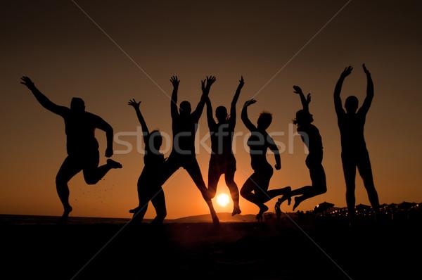 Boldog fiatalok csoport sziluettek ugrik tengerpart Stock fotó © IvicaNS