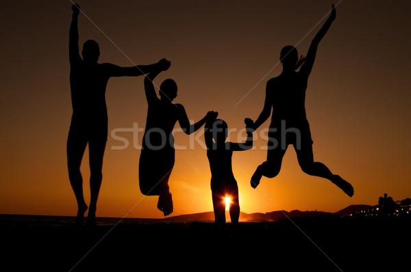 Naplemente sziluett család ugrik tengerpart gyönyörű Stock fotó © IvicaNS