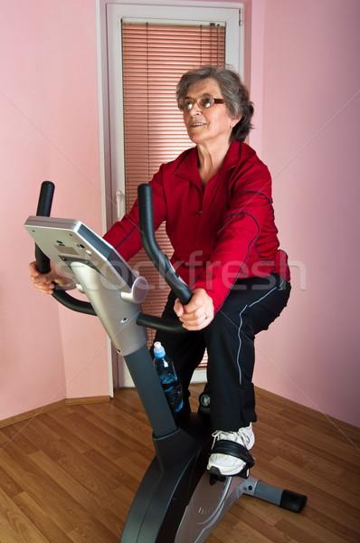 Boldog idős nő testmozgás bicikli otthon Stock fotó © IvicaNS
