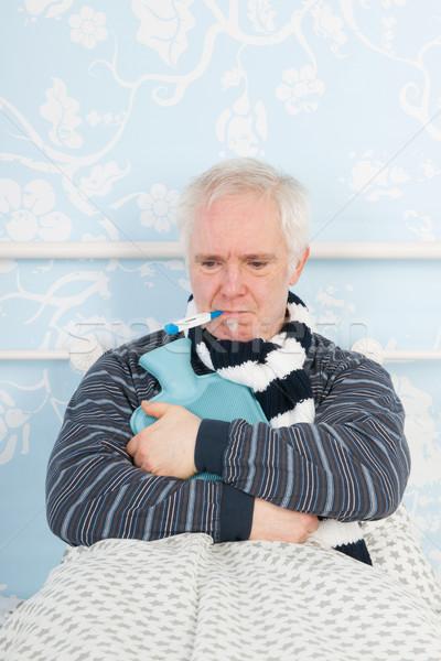 Senior man griep ziek bed heet water Stockfoto © ivonnewierink