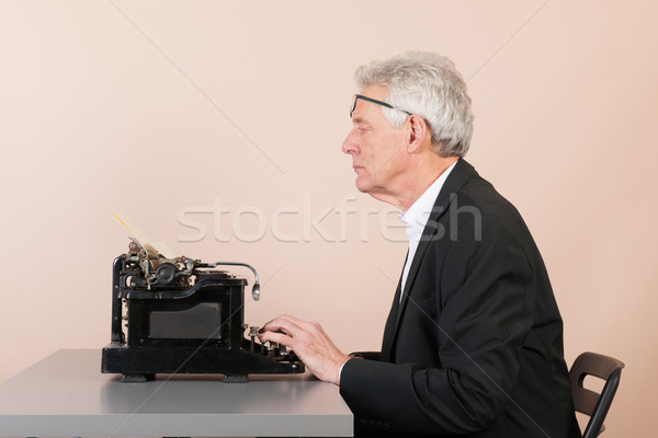 Man working with black typewriter Stock photo © ivonnewierink