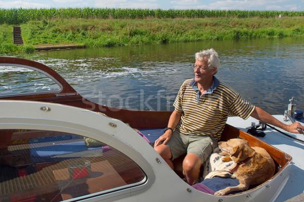 Uomo cane barca fiume estate Foto d'archivio © ivonnewierink