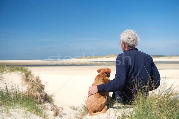 Man with dog on sand dune Stock photo © ivonnewierink