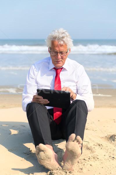 Stock fotó: üzletember · dolgozik · tabletta · tengerpart · hivatalos · öltöny