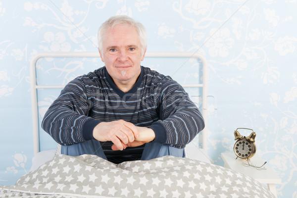 Człowiek piżama starszy posiedzenia bed okulary Zdjęcia stock © ivonnewierink