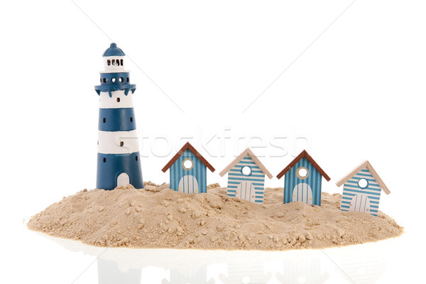Beach huts and lighthouse in the sand Stock photo © ivonnewierink