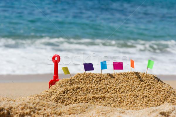 Homokvár tengerparti homok kastély színes zászlók tengerpart Stock fotó © ivonnewierink