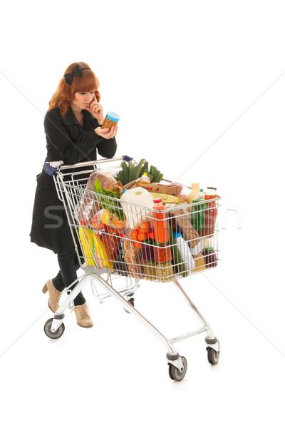Mulher completo carrinho de compras leitura etiqueta crítico Foto stock © ivonnewierink