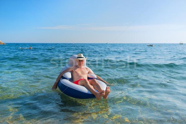 Idős férfi lebeg tenger vakáció szék Stock fotó © ivonnewierink