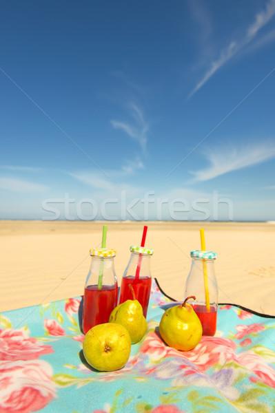 Bottles lemonade and fruit at beach Stock photo © ivonnewierink