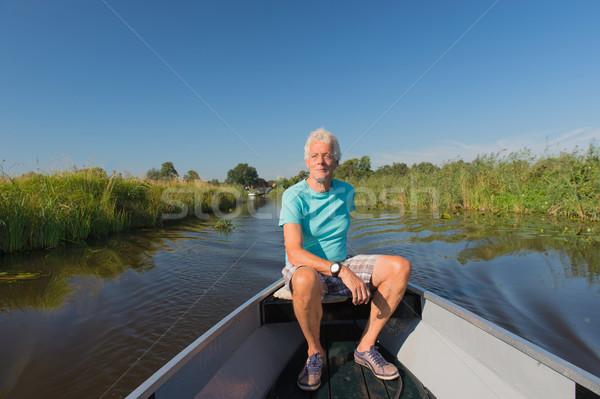 Starszy człowiek motorówka charakter wody lata Zdjęcia stock © ivonnewierink