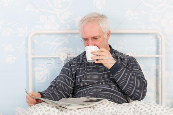 Senior man reading newspapers in bed Stock photo © ivonnewierink