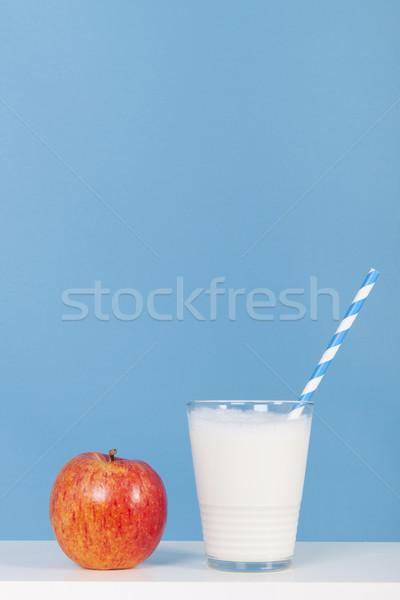 Glas of milk with apple on blue Stock photo © ivonnewierink