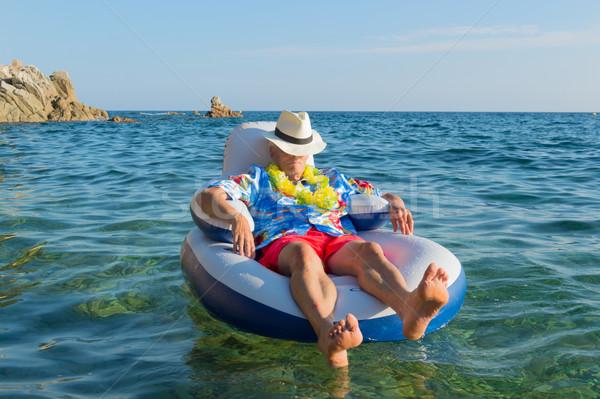 Senior man floating in sea Stock photo © ivonnewierink