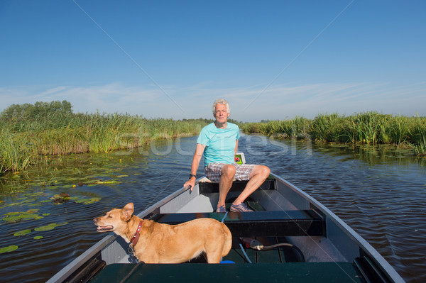 Senior man with dog in motor boat Stock photo © ivonnewierink