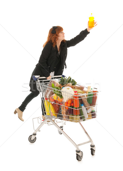 Woman with Shopping cart full dairy grocery picking the soap Stock photo © ivonnewierink