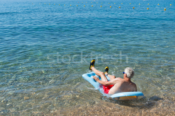 Jubilado hombre jugando mar agua inflable Foto stock © ivonnewierink