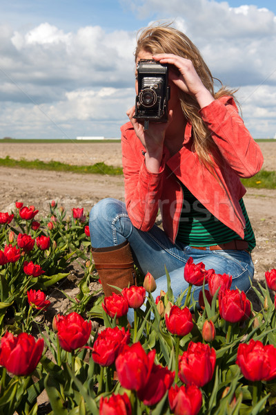 Dutch blond girl with old photo camera in field with tulips Stock photo © ivonnewierink